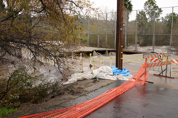 Floodwaters damaged Fashion Valley Road in Mission Valley across the San Diego River, perhaps signs to come as El Niño looms. (Courtesy of San River Park Foundation)