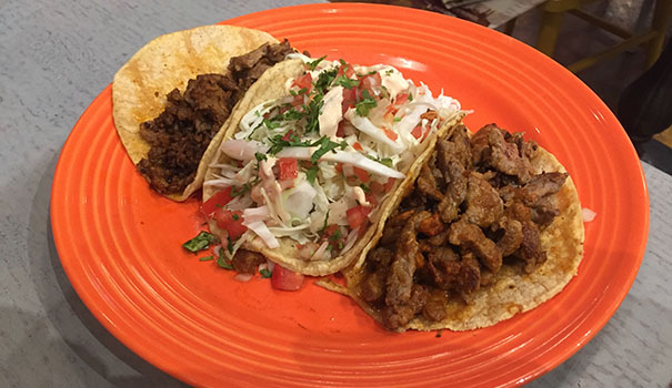Two beef tacos flanking one filled with beer-battered fish