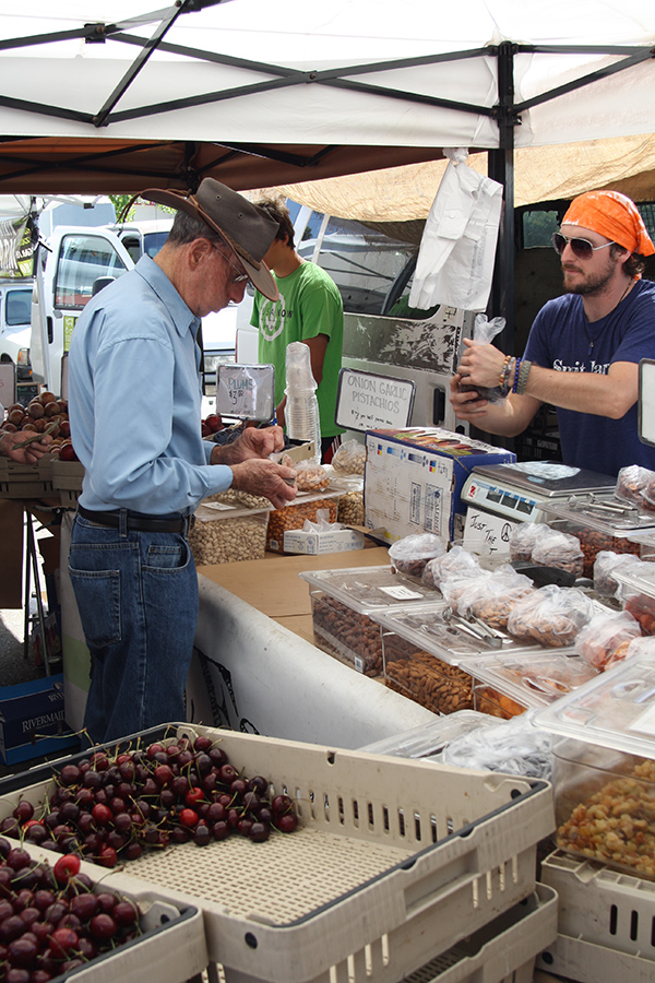A customer shops at the Smit Farms booth at the new farmers market in Serra Mesa. (Photo by Jeff Clemetson)