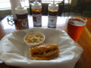 A half-sandwich of pulled pork and side of coleslaw paired to Eye of the Hawk amber ale (Photo by Dr. Ink)