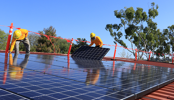Sullivan Solar Power technicians install panels on the roof of the San Diego Center for Children in Linda Vista. (Courtesy of Sullivan Solar Power)